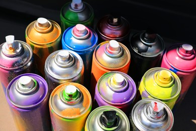 Many different used cans of spray paint, above view. Graffiti supplies