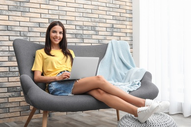 Young woman with modern laptop sitting on sofa at home