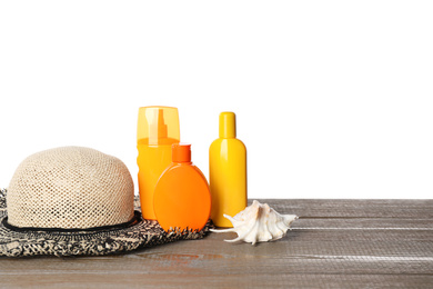 Sun protection products, hat and seashell on wooden table against white background. Space for text