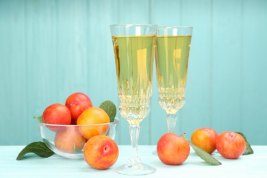 Delicious plum liquor and ripe fruits on table against light blue background. Homemade strong alcoholic beverage