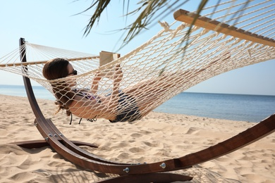 Young woman reading book in hammock on beach