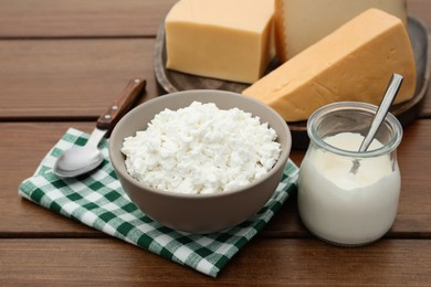 Tasty cottage cheese and other fresh dairy products on wooden table