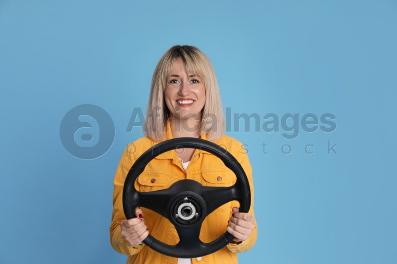 Happy woman with steering wheel on light blue background