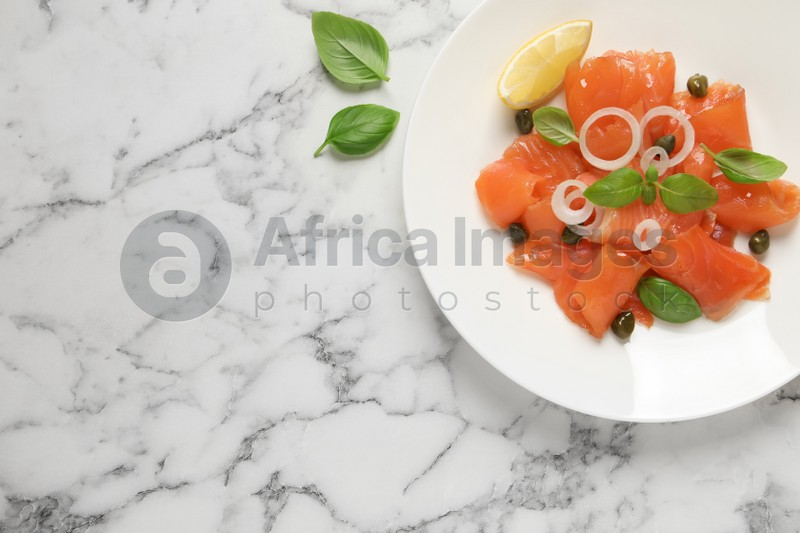 Delicious salmon carpaccio served on white marble table, flat lay. Space for text