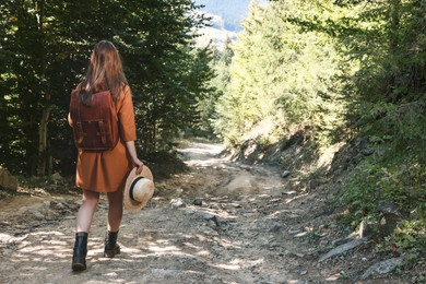 Woman with backpack and hat walking in forest, back view