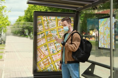 Young man in protective mask with smartphone and backpack waiting for public transport at bus stop