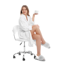 Young woman in bathrobe with cup of beverage on white background