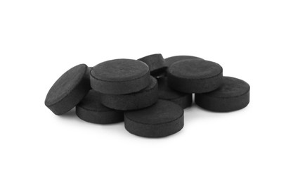 Activated charcoal pills on white background. Potent sorbent