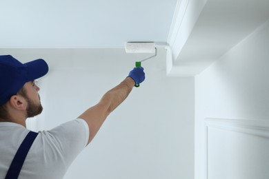 Handyman painting ceiling with white dye indoors, back view. Space for text