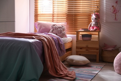 Bed with beautiful linens in children's room. Modern interior design