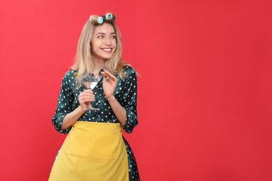 Young housewife with glass of martini on red background. Space for text
