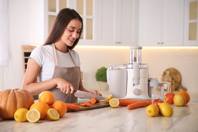 Young woman cutting fresh carrot for juice at table in kitchen