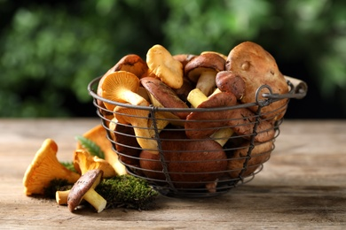 Different wild mushrooms on wooden table, closeup