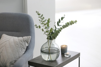 Vase with fresh eucalyptus branches on table in living room. Interior design