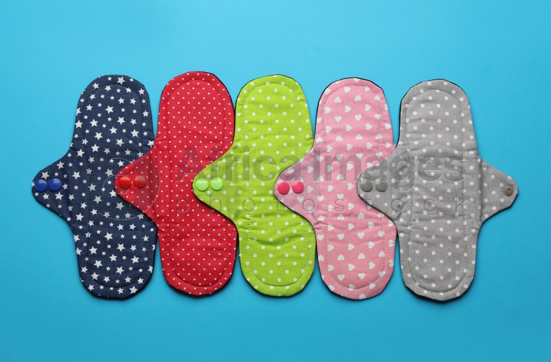 Many reusable cloth menstrual pads on light blue background, flat lay