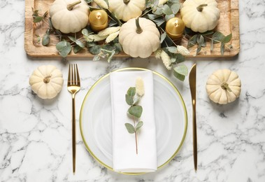 Festive table setting with autumn decor on white marble background, flat lay