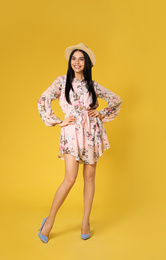 Young woman wearing floral print dress and straw hat on yellow background