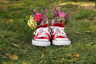 Shoes with beautiful flowers on grass outdoors
