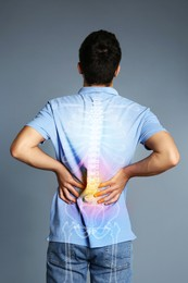 Man having backache on grey background. Digital compositing with illustration of spine