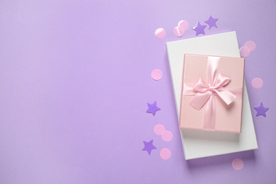 Beautiful gift boxes and confetti on violet background, flat lay. Space for text