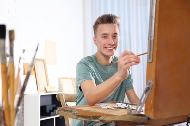 Teenage boy painting on easel in workshop, space for text. Hobby club