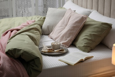 Cup of drink, cookies and book on bed with new pistachio linens