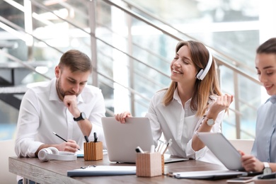 Young businesswoman with headphones, laptop and her colleagues working in office