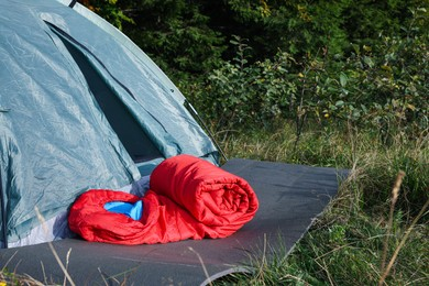 Red sleeping bag near camping tent on green grass outdoors, space for text