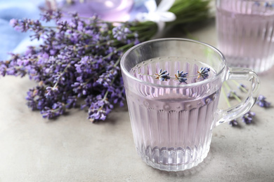 Fresh delicious drink with lavender in glass cup on grey table