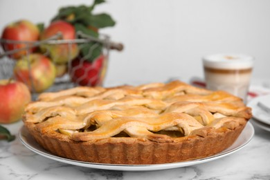 Delicious traditional apple pie on white marble table, closeup