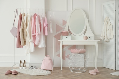 Dressing room interior with clothing rack and round mirror