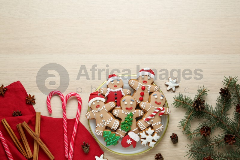 Flat lay composition with delicious Christmas cookies on beige wooden table, space for text