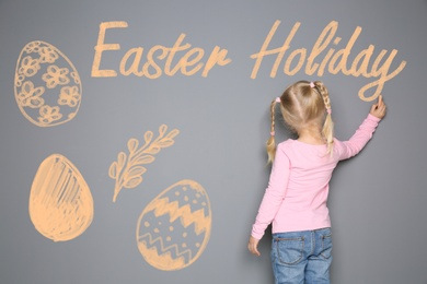 Small girl writing phrase Easter Holiday on grey wall with drawings. School holiday