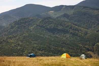 Camping tents in mountains on sunny day