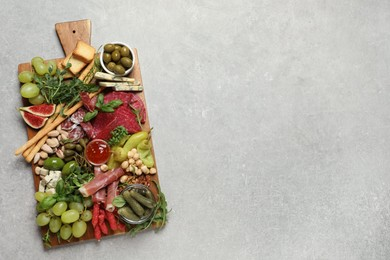 Set of different delicious appetizers served on light grey table, top view. Space for text