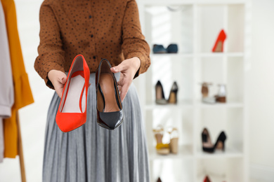 Female business owner showing shoes in boutique, closeup. Space for text