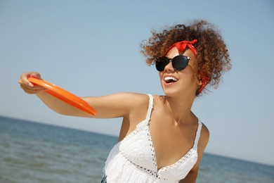 Happy African American woman throwing flying disk at beach on sunny day