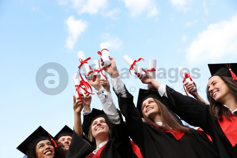 Happy students with diplomas outdoors. Graduation ceremony