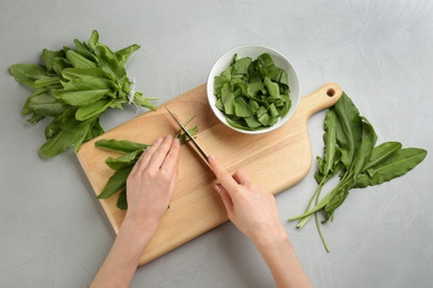Woman cutting sorrel leaves at light grey table, top view