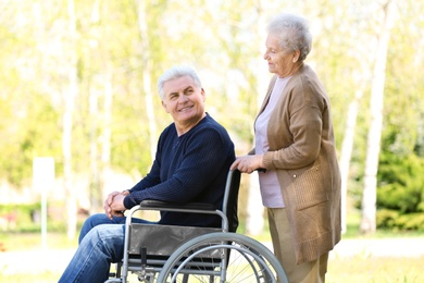Mature man in wheelchair and senior woman at park on sunny day