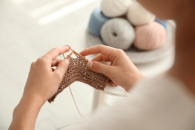 Young woman knitting with needles indoors, closeup. Engaging in hobby
