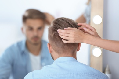 Professional hairdresser working with young man in barbershop. Trendy hair color