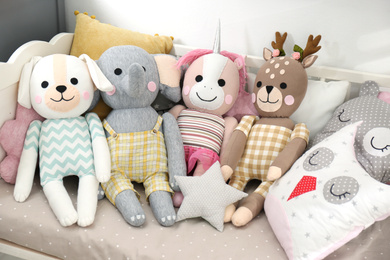 Cute toys and pillows on bed in baby room. Interior elements