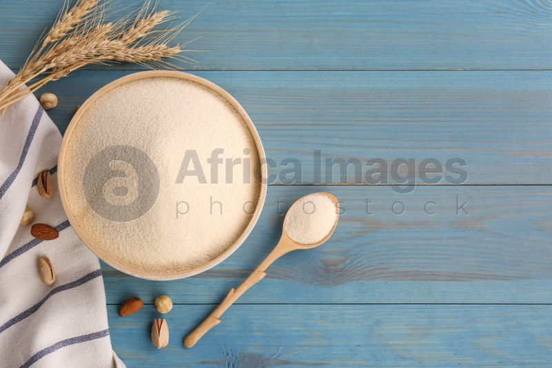 Uncooked organic semolina, spikelets and nuts on light blue wooden table, flat lay. Space for text