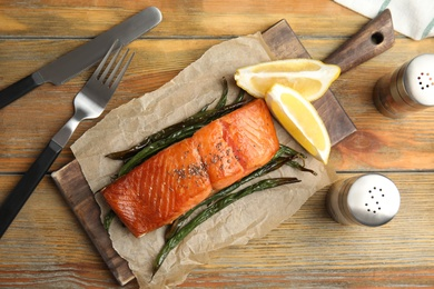 Tasty cooked salmon and vegetables served on wooden table, flat lay. Healthy meals from air fryer