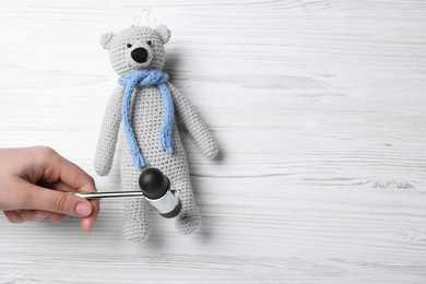 Woman pretending to test teddy bear's reflexes with hammer on white wooden background, top view and space for text. Nervous system diagnostic