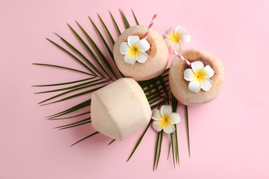 Fresh coconuts with drinking straws and flowers on pink background, flat lay