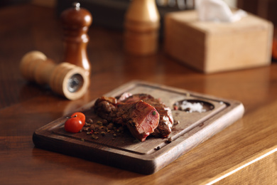Tasty roasted meat served on wooden table. Cooking food