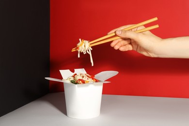 Woman eating vegetarian wok noodles with chopsticks from box on color background, closeup