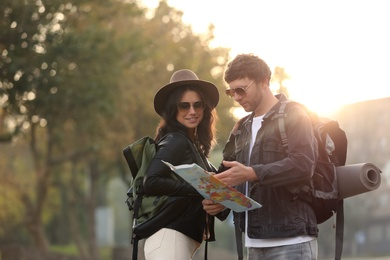 Couple of travelers with map on city street